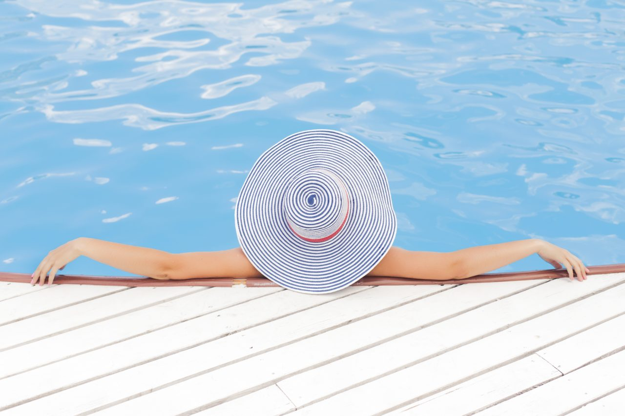 Lady in pool with sunhat